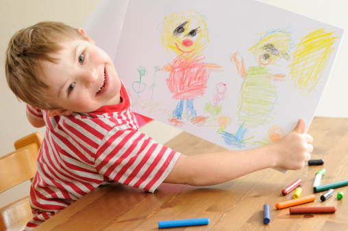 Boy with Down Syndrome shows his drawing